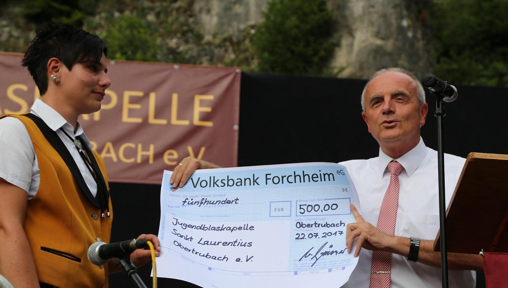 Bürgermeister Markus Grüner überreicht einen Scheck im Namen der Gemeinde
